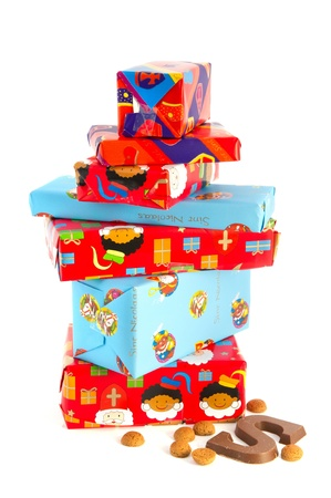 Stacked dutch Sinterklaas presents with typical candy isolated over white background photo
