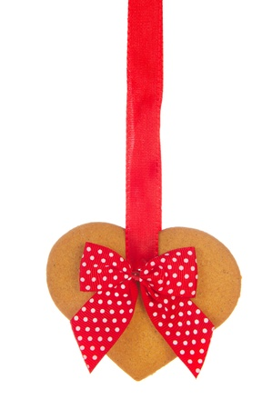 Ginger bread heart hanging at red ribbon photo