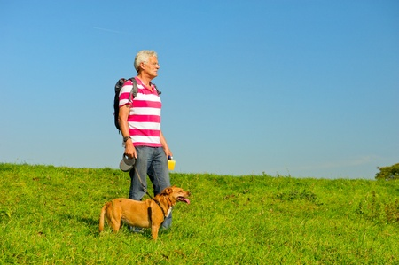Hiking elderly man with dog in nature environment