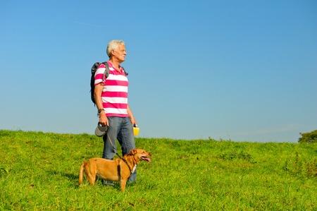 Wandelen oudere man met hond in de natuur omgeving