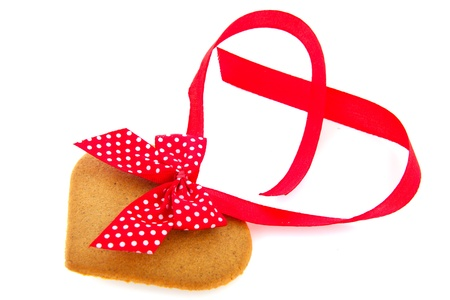 Ginger bread heart for Christmas with red ribbon and bow photo