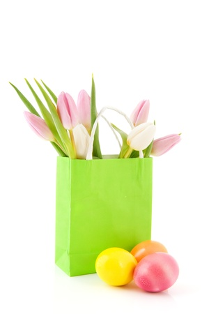 Colored easter eggs with bouquet tulips in green paper bag photo