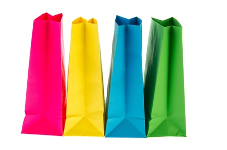 Row colored empty paper bags in pink, yellow, blue and green photo