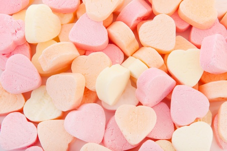 Colorful candy hearts in pink yellow and orange as background photo