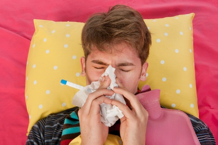 Very ill man islaying in his bed with warm water bottle and thermometer while blowing his nose photo