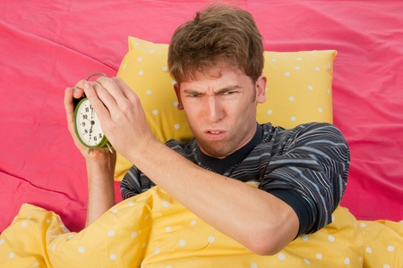 man is waking up with alarm clock with bells photo