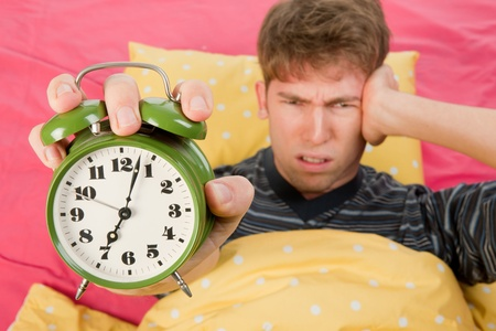 striped pajamas: man is waking up with alarm clock with bells