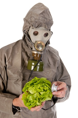 Man dressed in protection suit and gas mask is exploring vegetables photo