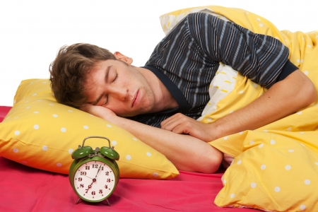 pillow sleep: Sleeping handsome young man with alarm clock