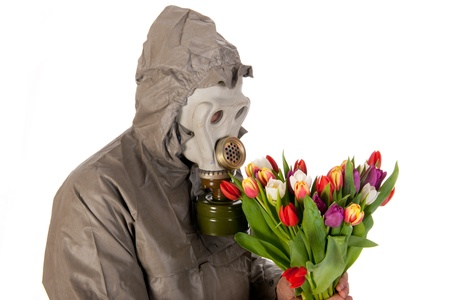 Man dressed in protection suit and gas mask with colorful flowers photo