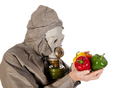 Man dressed in protection suit and gas mask is holding vegetables photo