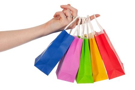 Hand hält viele bunte Einkaufstaschen