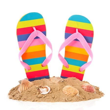 sandalias: Flip flop con rayas de colores en la playa del verano Foto de archivo