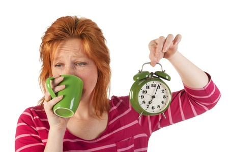 seven o'clock: Young woman is enjoying het morning coffee while wake up very early