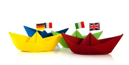 Colorful folded paper boats with European flags isolated over white background photo