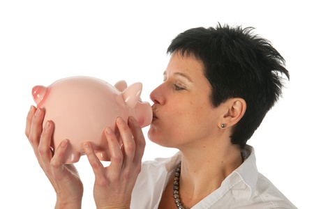 Young woman holding and kissing a piggy bank as studio portrait Stock Photo - 12729481