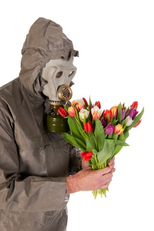 Man dressed in protection suit and gas mask with bouquet flowers photo