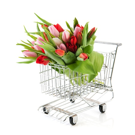 Shopping cart with bouquet colorful tulips isolated over white background photo