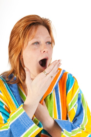 striped pajamas: Yawning young woman in colorful gowne with hood Stock Photo
