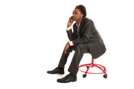 black business man: Jeune homme d'affaires noir avec un t�l�phone mobile assis dans le studio