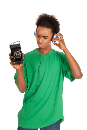 teenager boy is with headphones connecting to vintage photo camera Stock Photo - 12950175