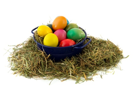 Blue bucket with straw and colorful painted easter eggs photo