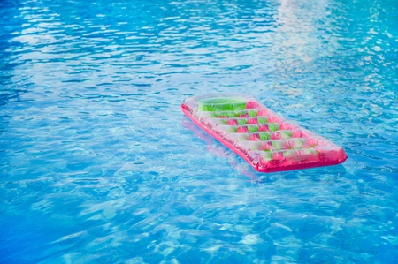 Floating pink and green air mattress in swimming pool photo