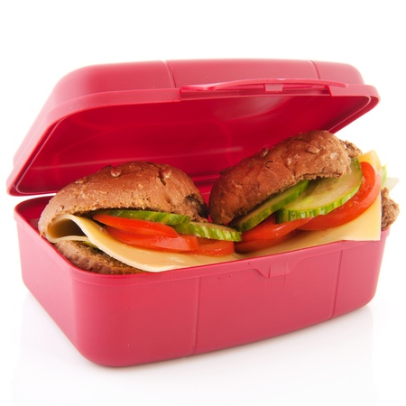 Pink lunchbox with healthy brown bread rolls cheese and vegetables