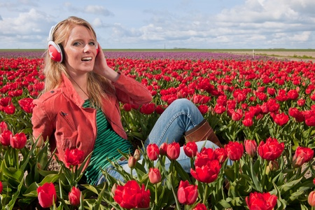 Portrait of a beautiful blond Dutch girl listening to music in tulips field photo