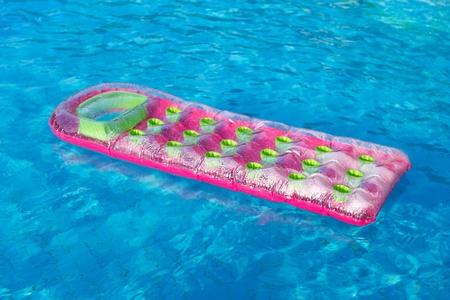 スイミング プールでピンクとグリーンのエアマットレスをフローティング