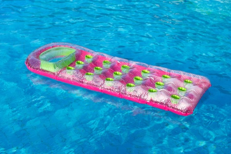 Floating pink and green air mattress in swimming pool 版權商用圖片