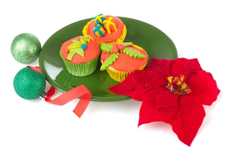 Colorful Christmas cupcakes on green platewith balls and poinsettia Stock Photo - 13468437