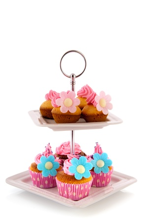 cupcakes isolated: Colorful cupcakes with pink icing on cake layer