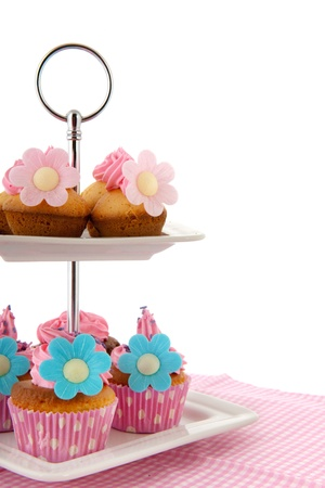 Colorful cupcakes with pink icing on cake layer photo