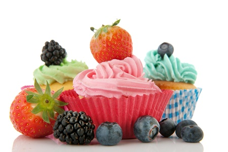 Colorful cupcakes with fresh fruit isolated over white background Stock Photo