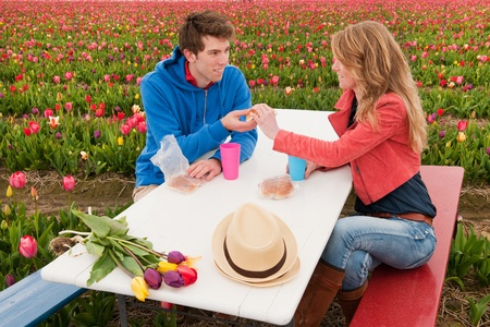 Young couple is having picnic in Dutch flower fields photo