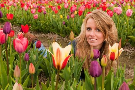 dutch girl: Portrait of a beautiful blond Dutch girl laying down in tulips field Stock Photo