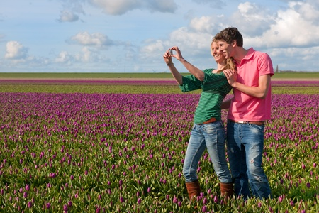 picture person: Couple Dutch tourists are taking pictures in the flower fields