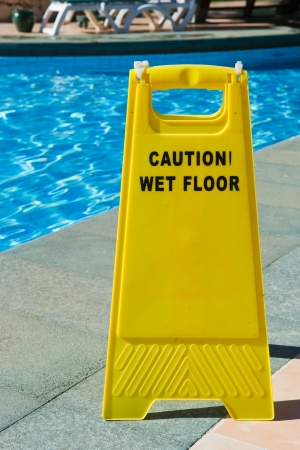 Sign with caution wet floor near the swimming pool Stock Photo - 13643491