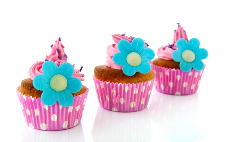 Pink cupcakes with blue flowers isolated over white background photo