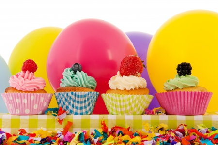 Colorful cupcakes with butter cream fruit and balloons for birthday photo