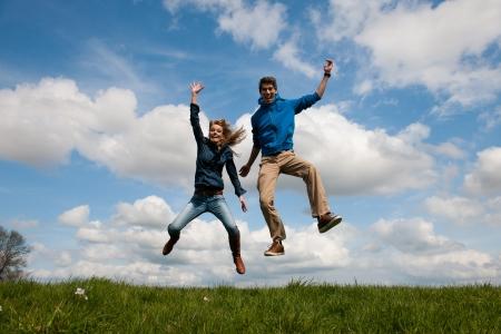 salto largo: Feliz saltando al aire libre pareja en los campos