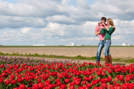 Young couple is taking pictures in Holland from flower fields photo