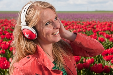 Dutch girl with long blond hair is listening to music photo