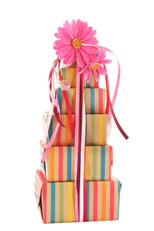 colorful stack with wrapped presents and flowers isolated on white background photo