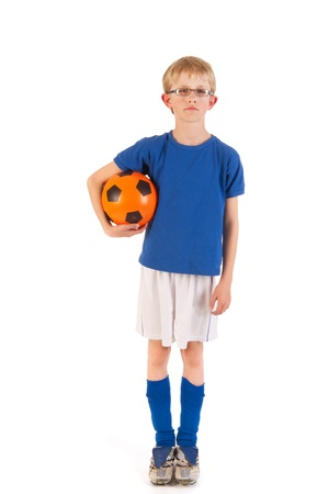 Little blond boy soccer player with ball in the studio photo