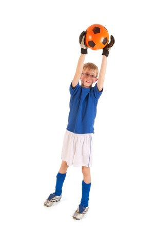 Little blond boy is playing soccer in the studio photo