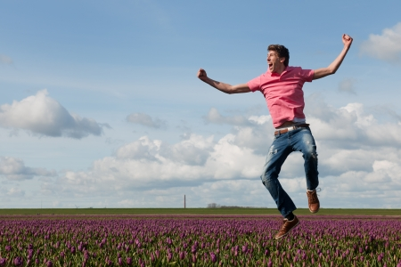 Young man is jumping above the typical dutch tulips photo