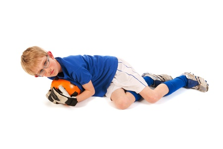Little blond boy is playing soccer keeper in the studio photo