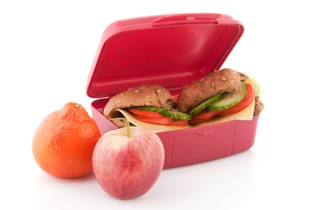 Pink lunchbox with healthy brown bread rolls cheese vegetables and fruit photo